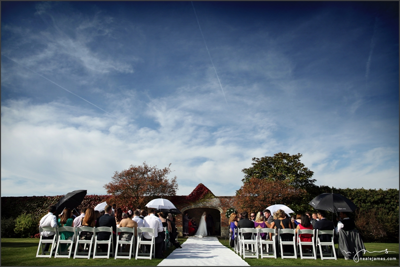 Guests use umbrellas to provide shade from the sun during an outdoor wedding ceremony at Notley Abbey