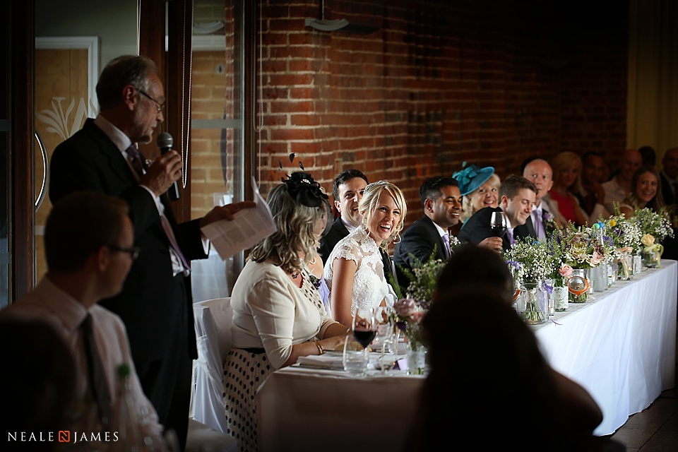 Bride laughing at a wedding speech