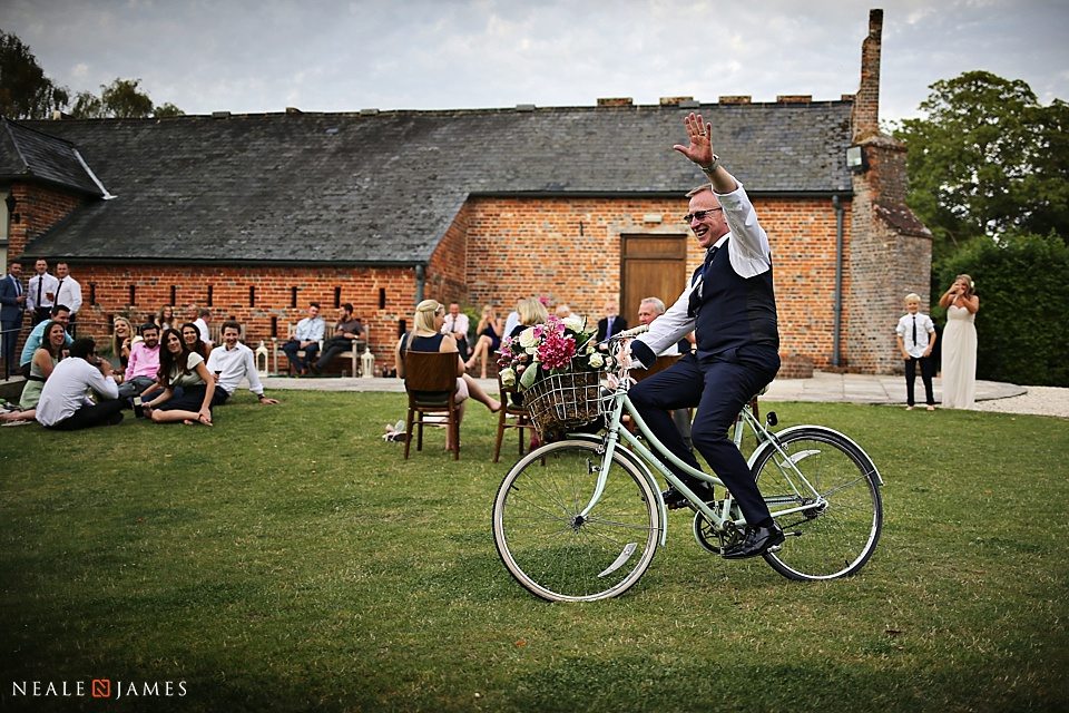 Colour image of a man riding a bicycle at a wedding for fun