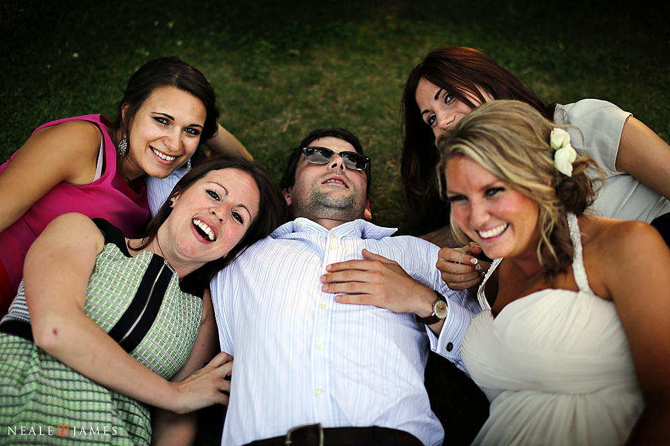 Wedding guests laying on the grass laughing