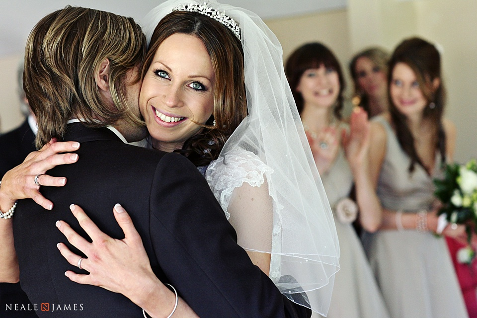 A happy bride hugs her new husband