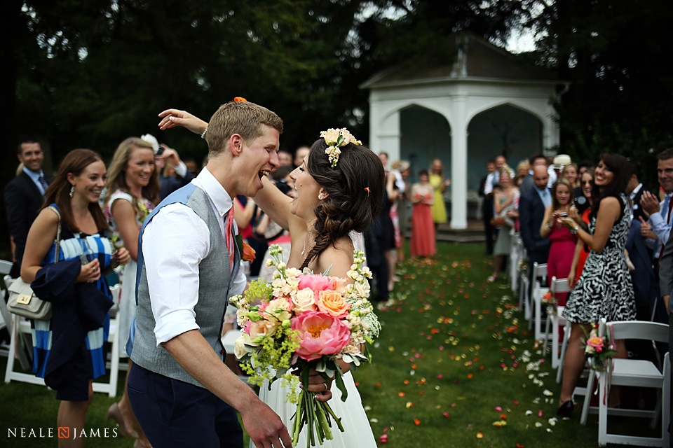 Colour photo of a couple marrying in the garden at Wasing Park
