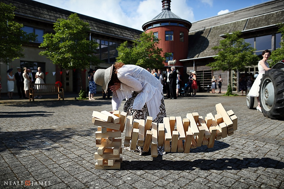 Colour photo of lady playing Giant Jenga game at Sheepdrove Farm