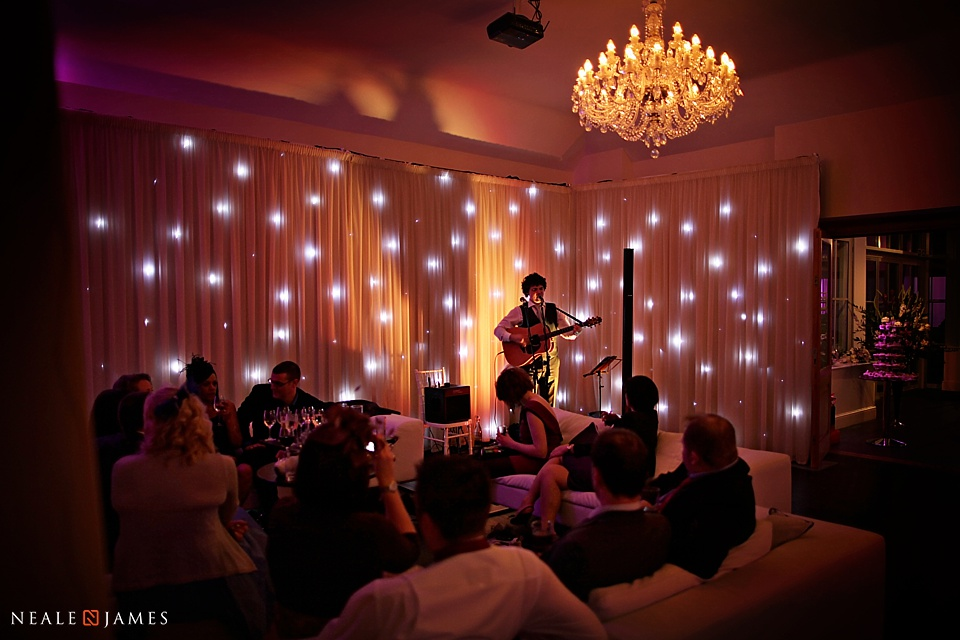 Evening party photo from Botleys Mansion, a man plays a guitar