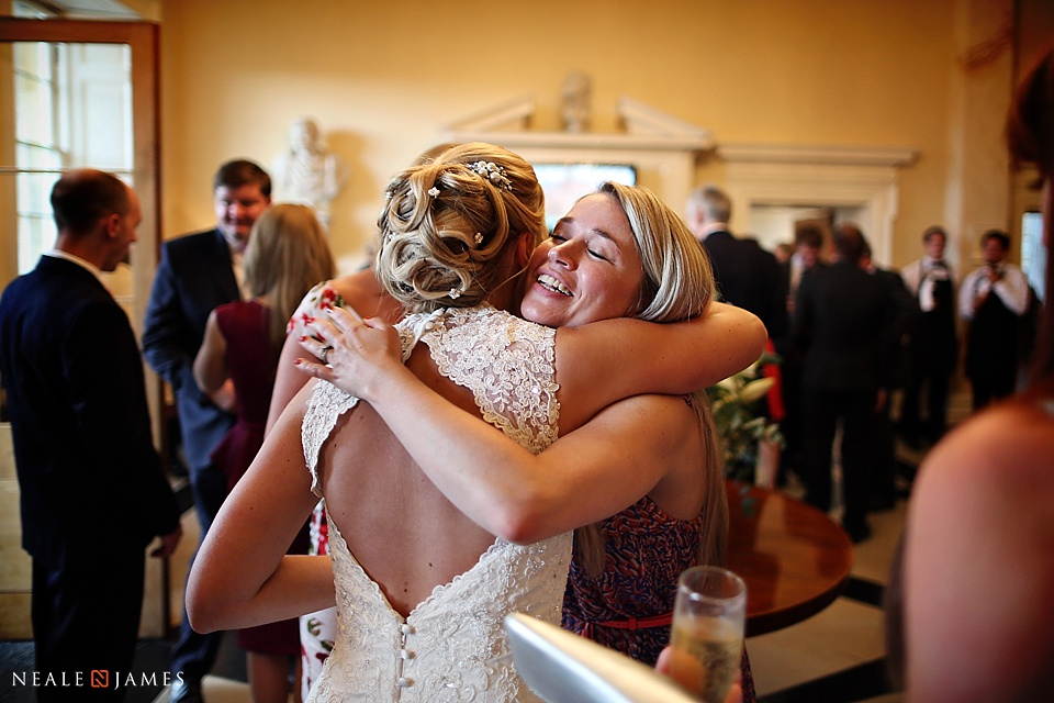 Colour photo of wedding guests hugging