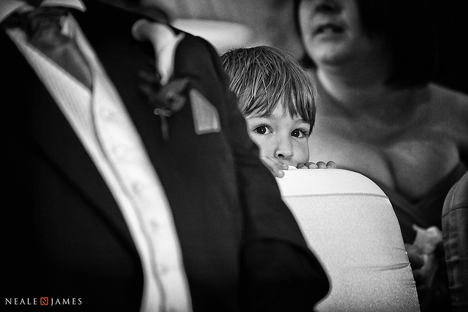 Black and white photograph of a boy in the ceremony room at a wedding