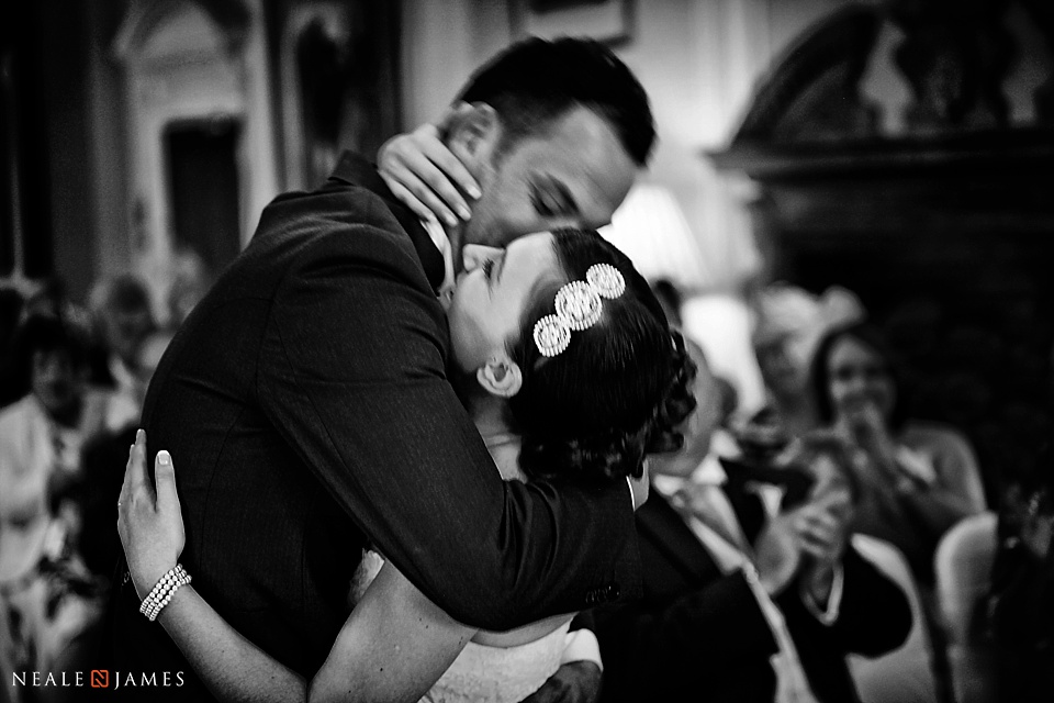 Black and white photo of bride and groom hugging at Horwood House