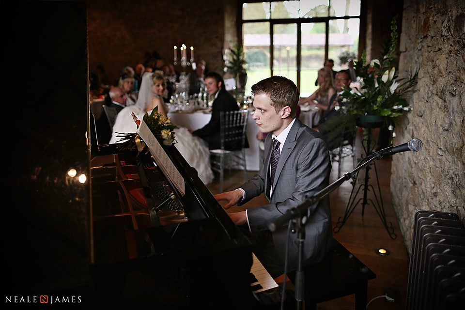 Photograph of the piano being played at Notley Abbey in the dining barn