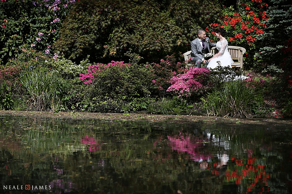 Colour image of a couple talking on a bench on their wedding day