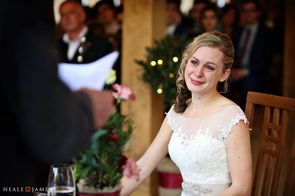 Colour image of a reading at a wedding with the bride's reaction