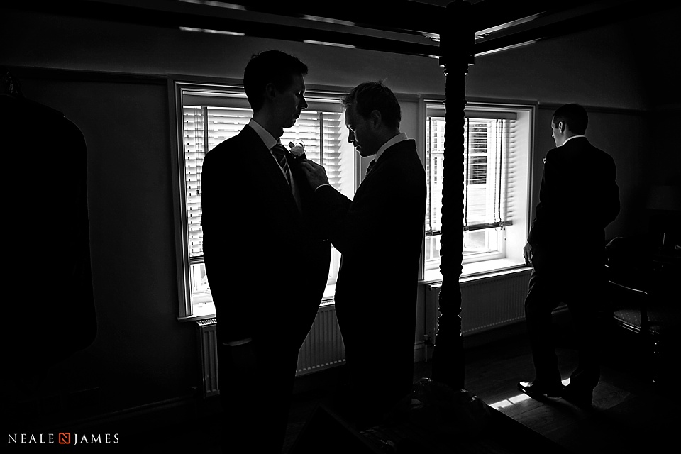 Black and white silhouette image of a bridegroom preparing for his day