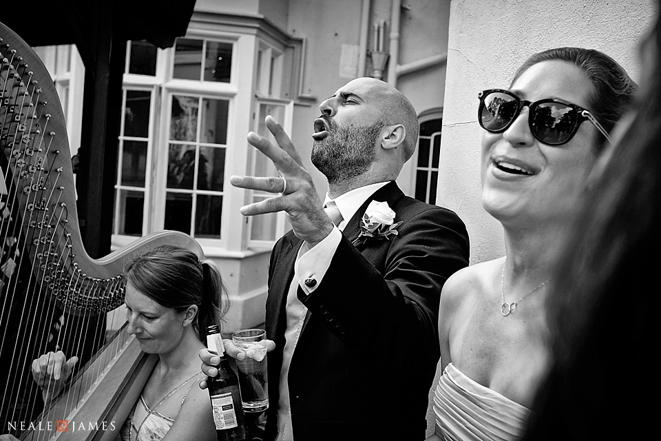 Monochrome image of a couple singing to music at a wedding