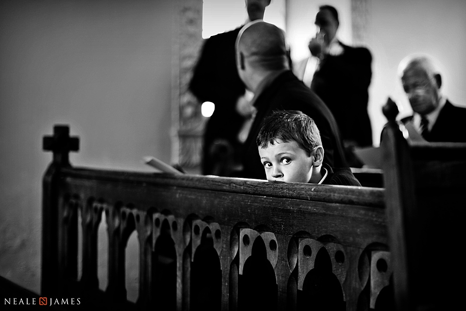 A boy waits in the pews at St Nicholas Church, Wasing Park