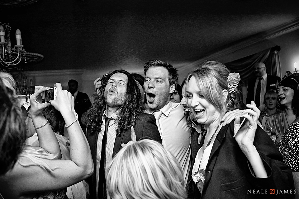 Black and white photo of wedding guests on the dance floor