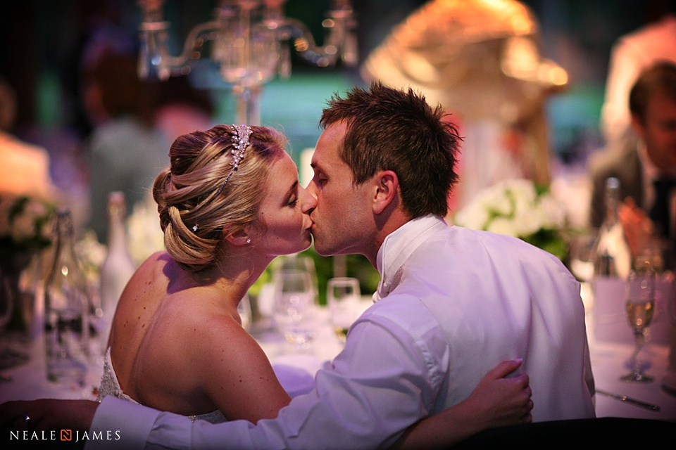Photograph of a bride and groom at Notley Abbey kissing during the wedding speeches