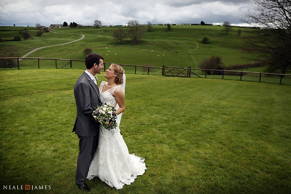 A paddock in Kingscote Barn's grounds with a bride and groom standing in it