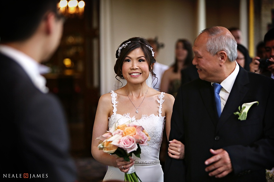 Photograph of bride walking into ceremony at Audleys Wood wedding venue