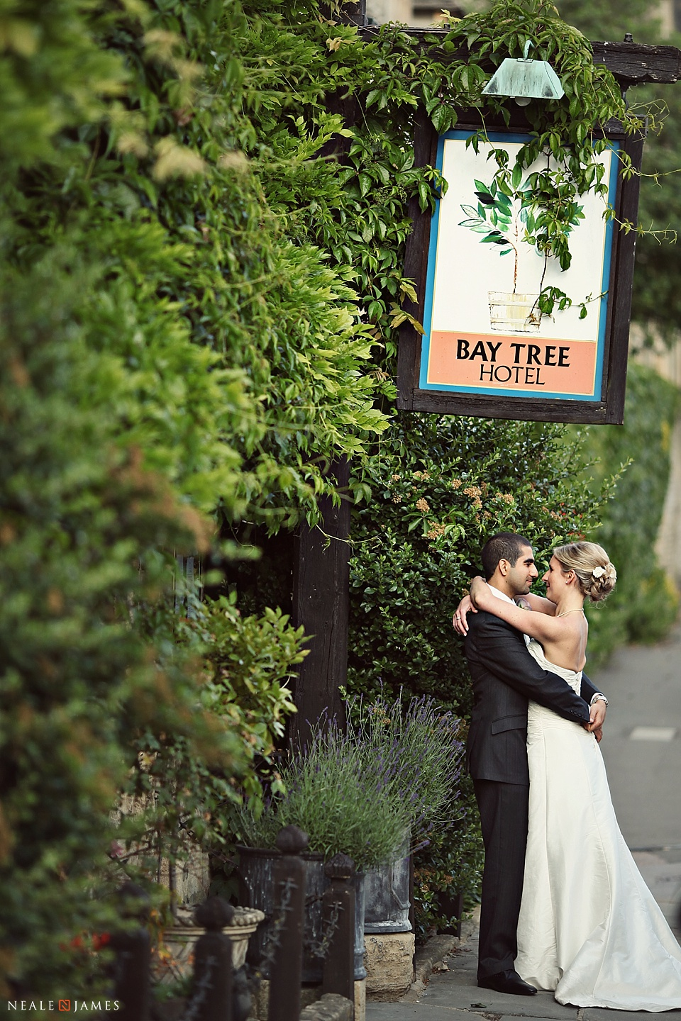 Colour photo of couple outside Bay Tree Hotel, Burford