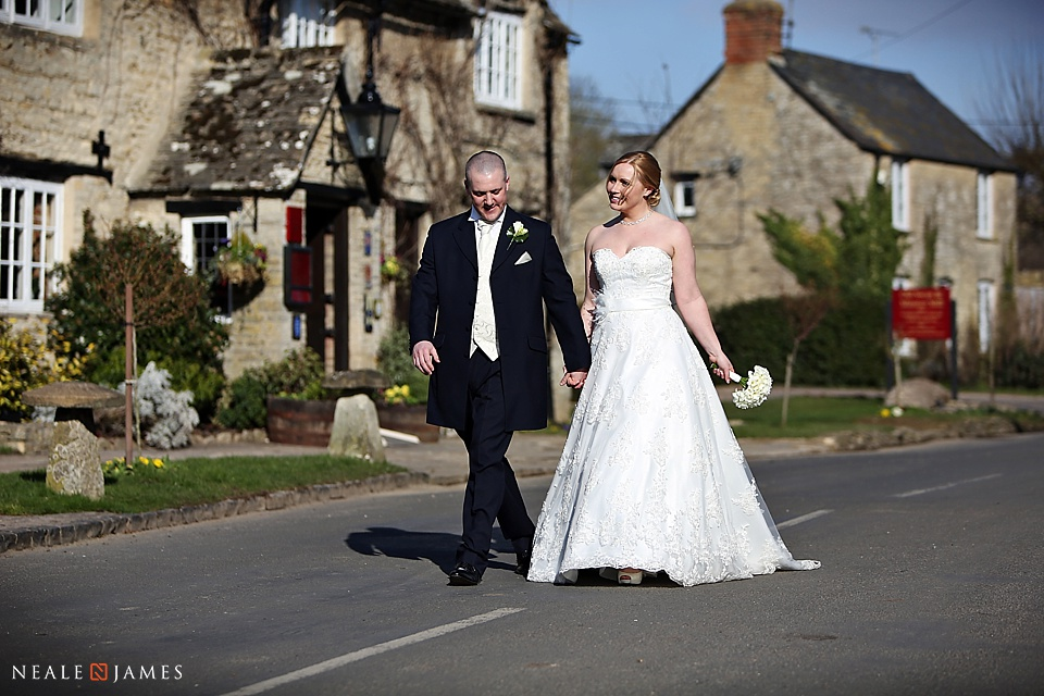 Colour image of bride and groom walking on road outside Old Swan and Minster Mill