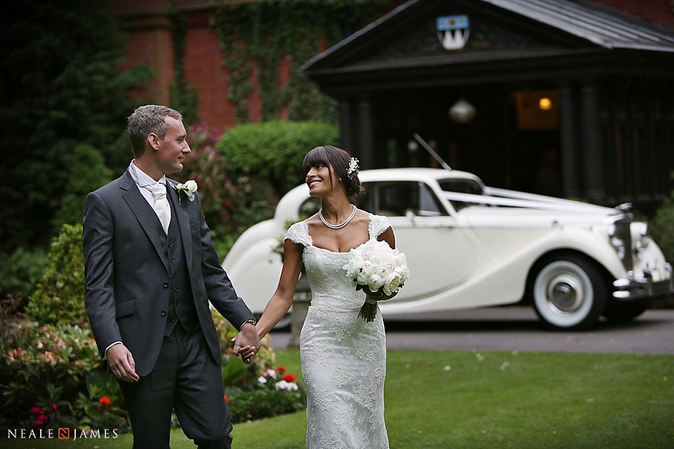 Colour picture of a wedding couple in front of a white vintage car