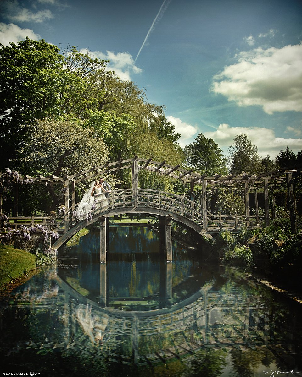 Blue skies and fluffy clouds frame a bride and groom on the bridge and Great Fosters