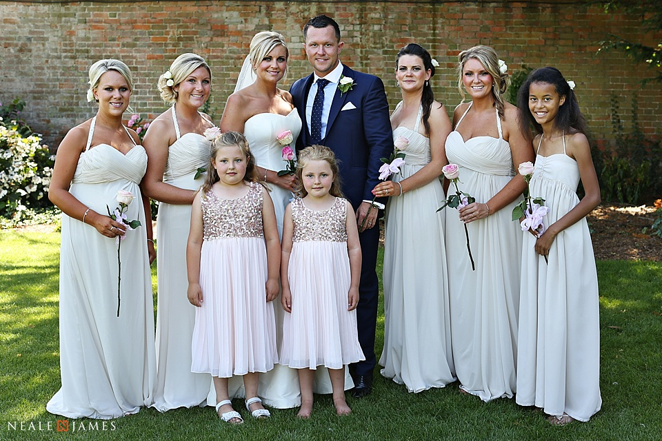 Colour photograph of the bridal party posing together at Wasing Park wedding venue