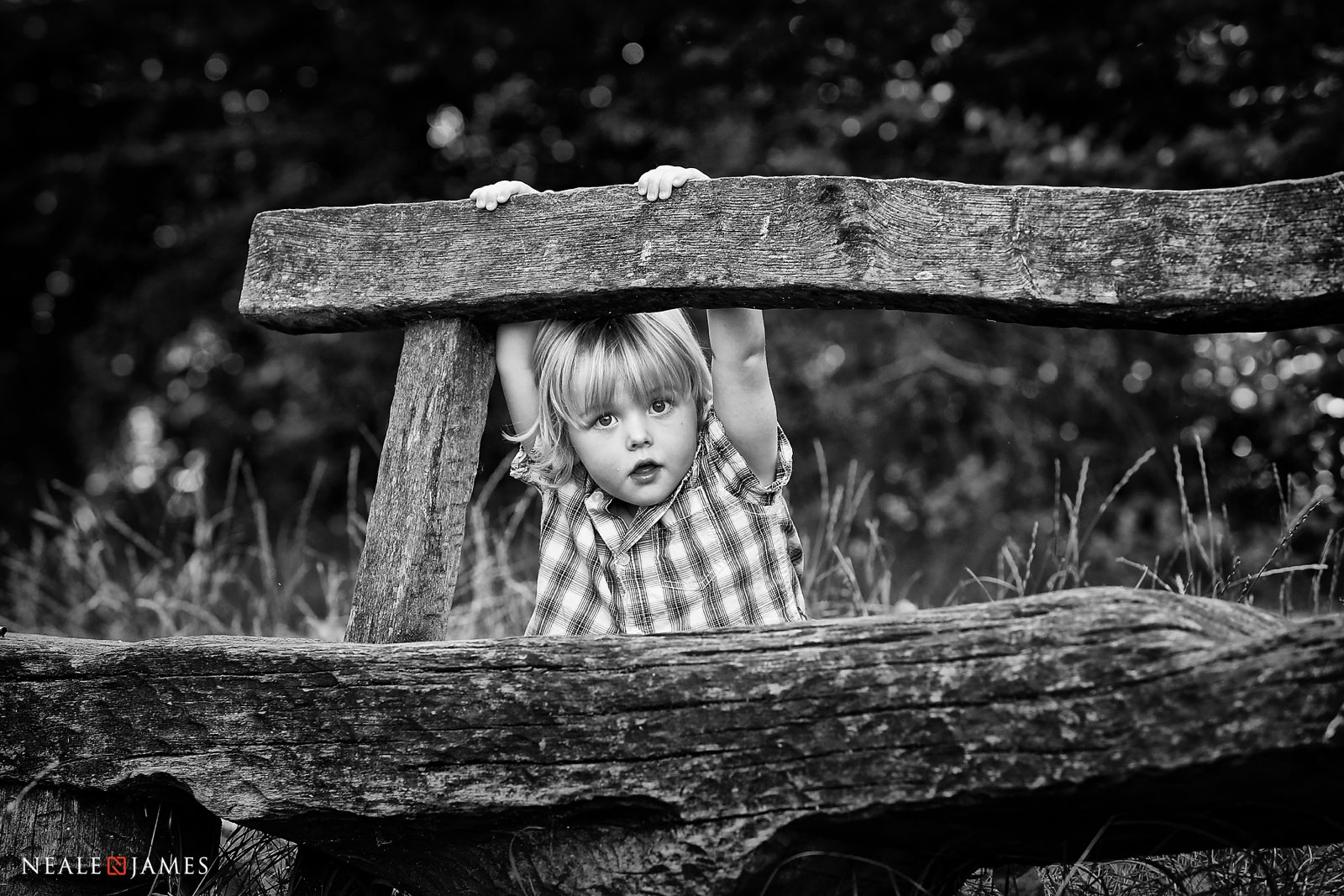 Monochrome photo of a boy on a park bench