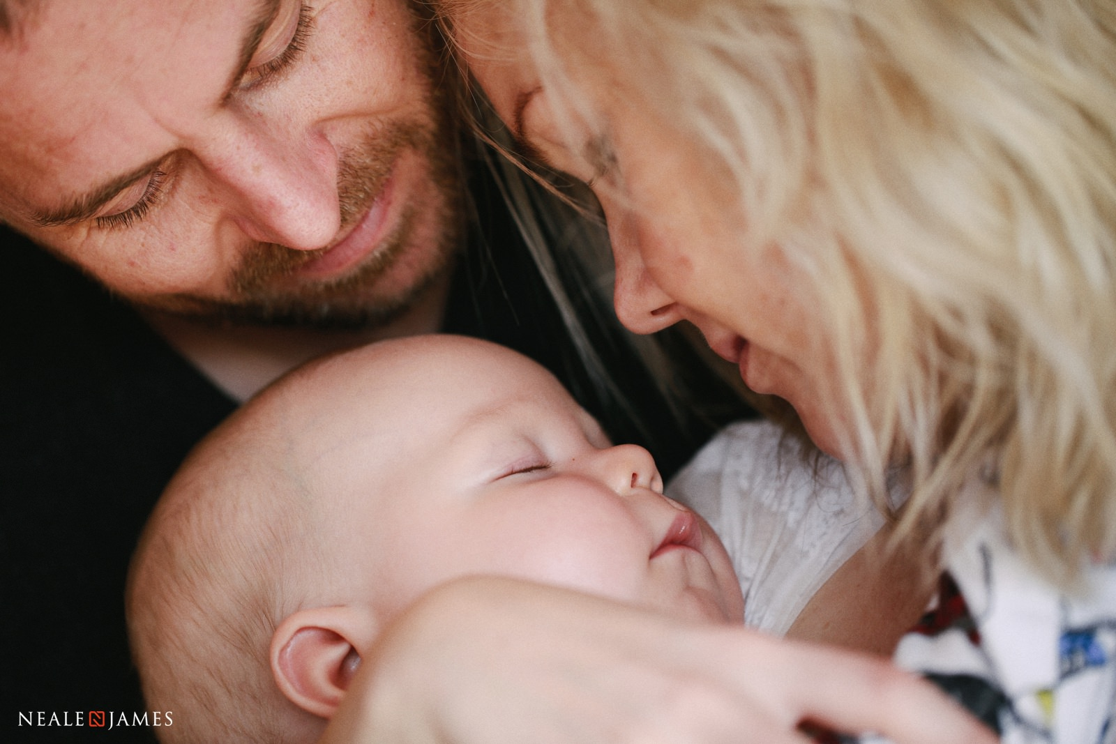 A colour photo of a baby, mother and father