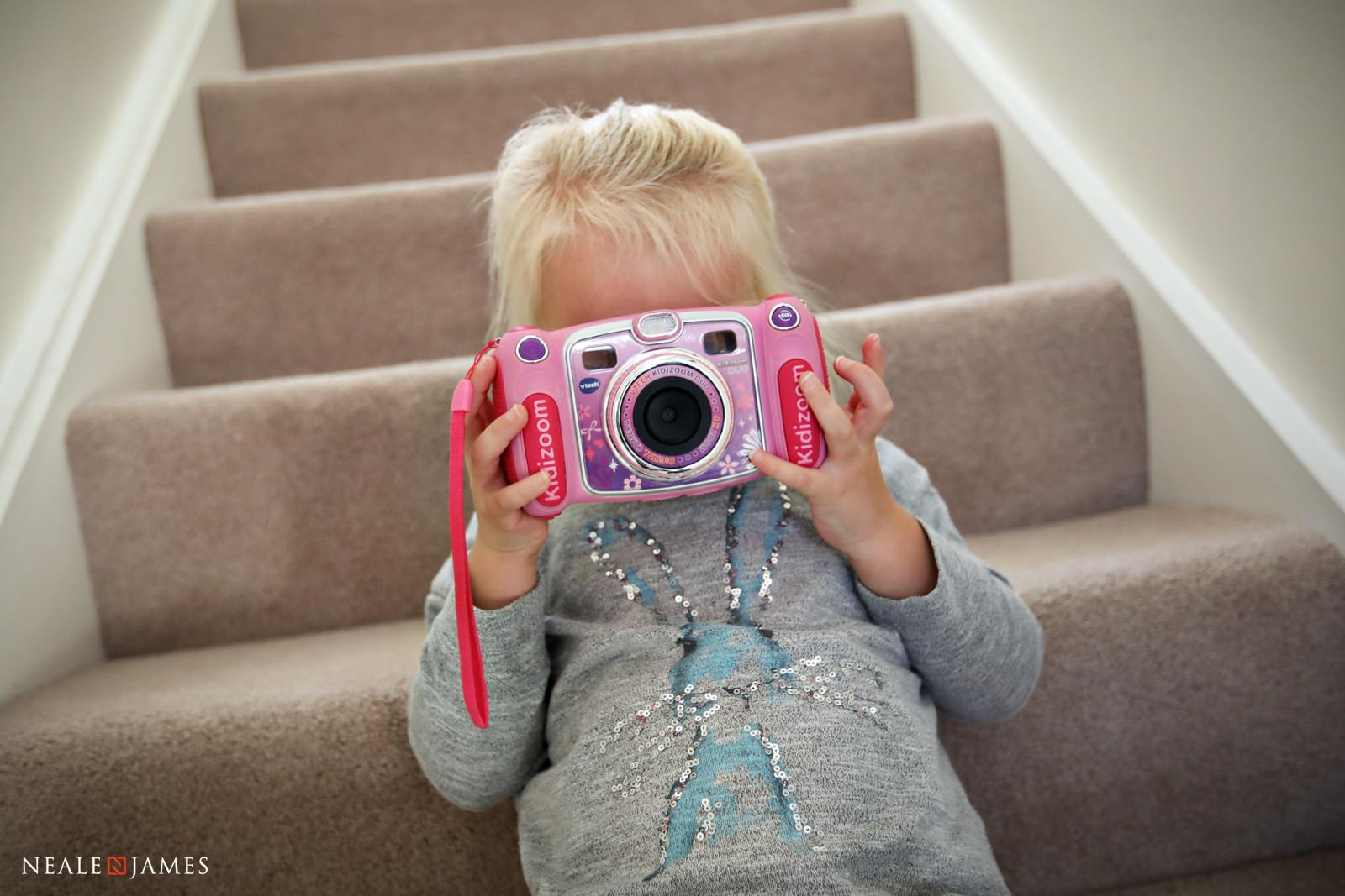 A colour photo of a girl taking a picture