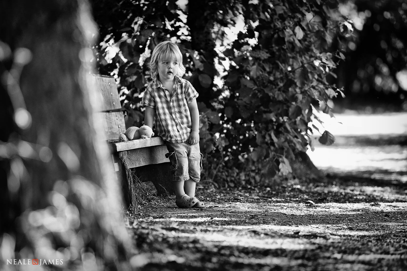 Monochrome picture of a boy by a park bench