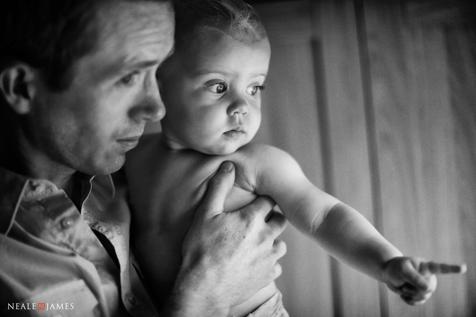 Black and white of a father looking out of the window with his daughter