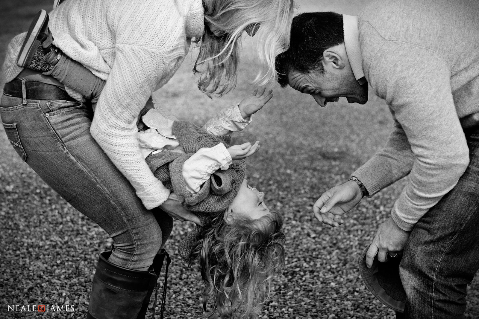 Monochrome picture of mother and father playing with their child