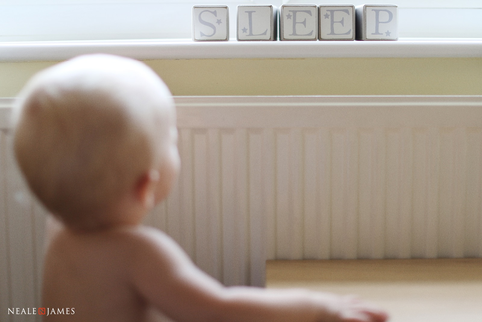 Colour photo of a baby looking at the word 'Sleep'