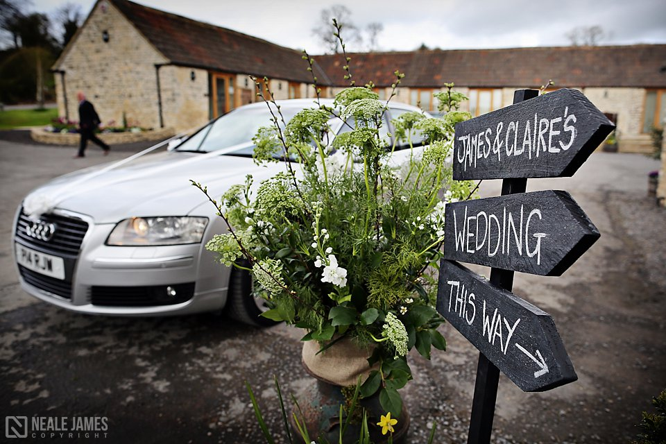 A black wooden sign points guests towards James and Claire's wedding at Kingscote Barn