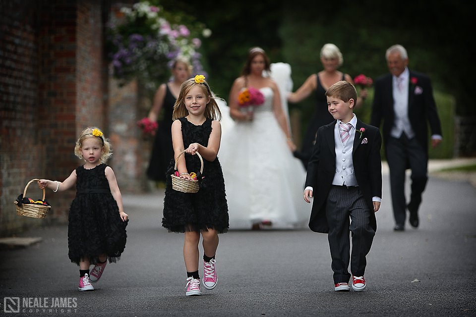 Two flowergirls and a page boy lead the bride and her bridesmaids at Wasing Park