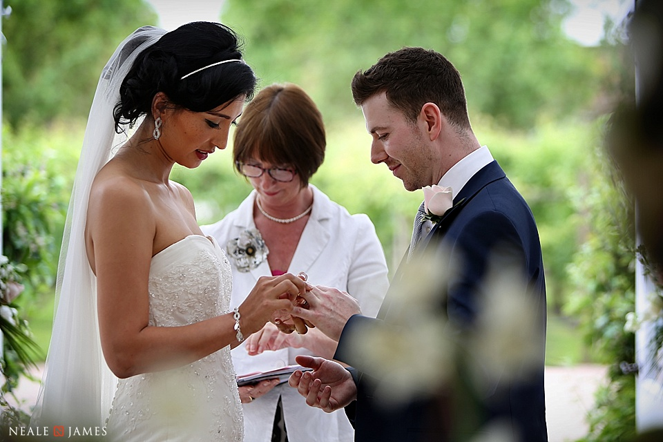 Exchanging vows during a civil ceremony at Combermere Abbey