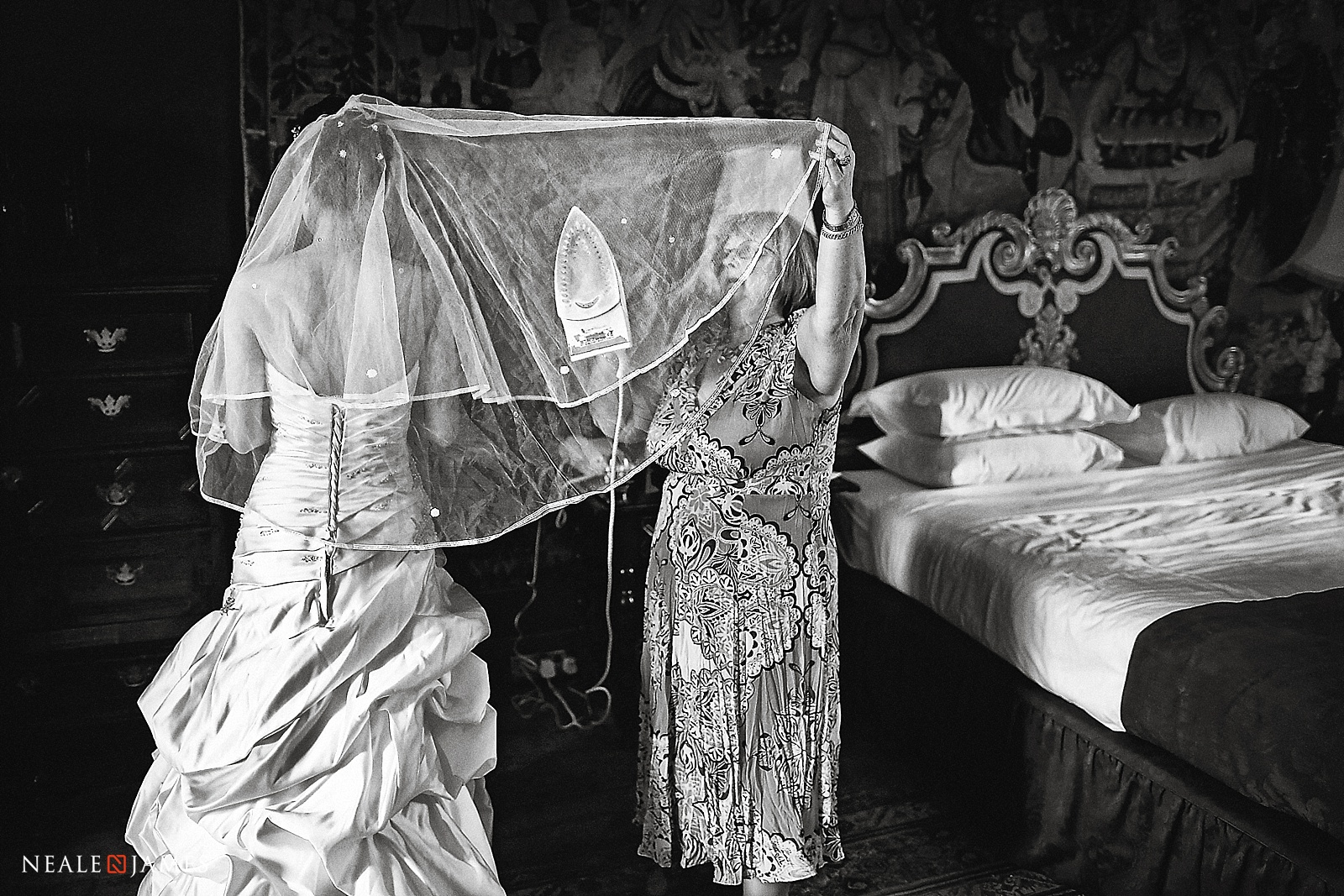 Black and white picture of wedding dress being ironed