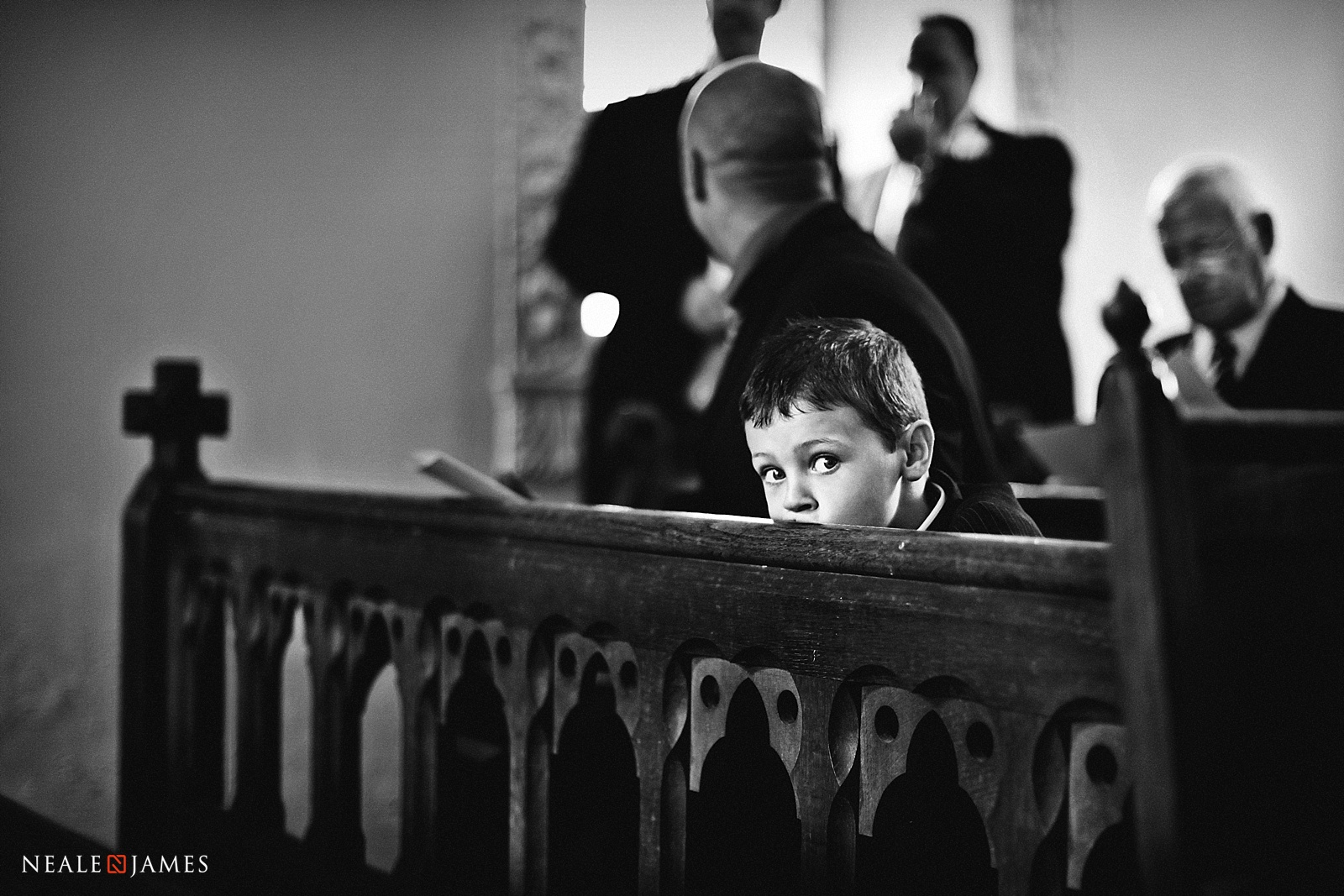 Black and white picture of a boy waiting in church for a wedding
