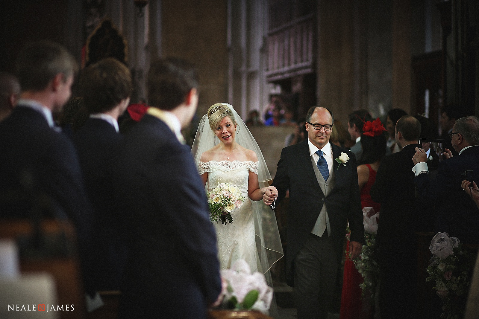 A father walks her daughter down the aisle in this colour photograph