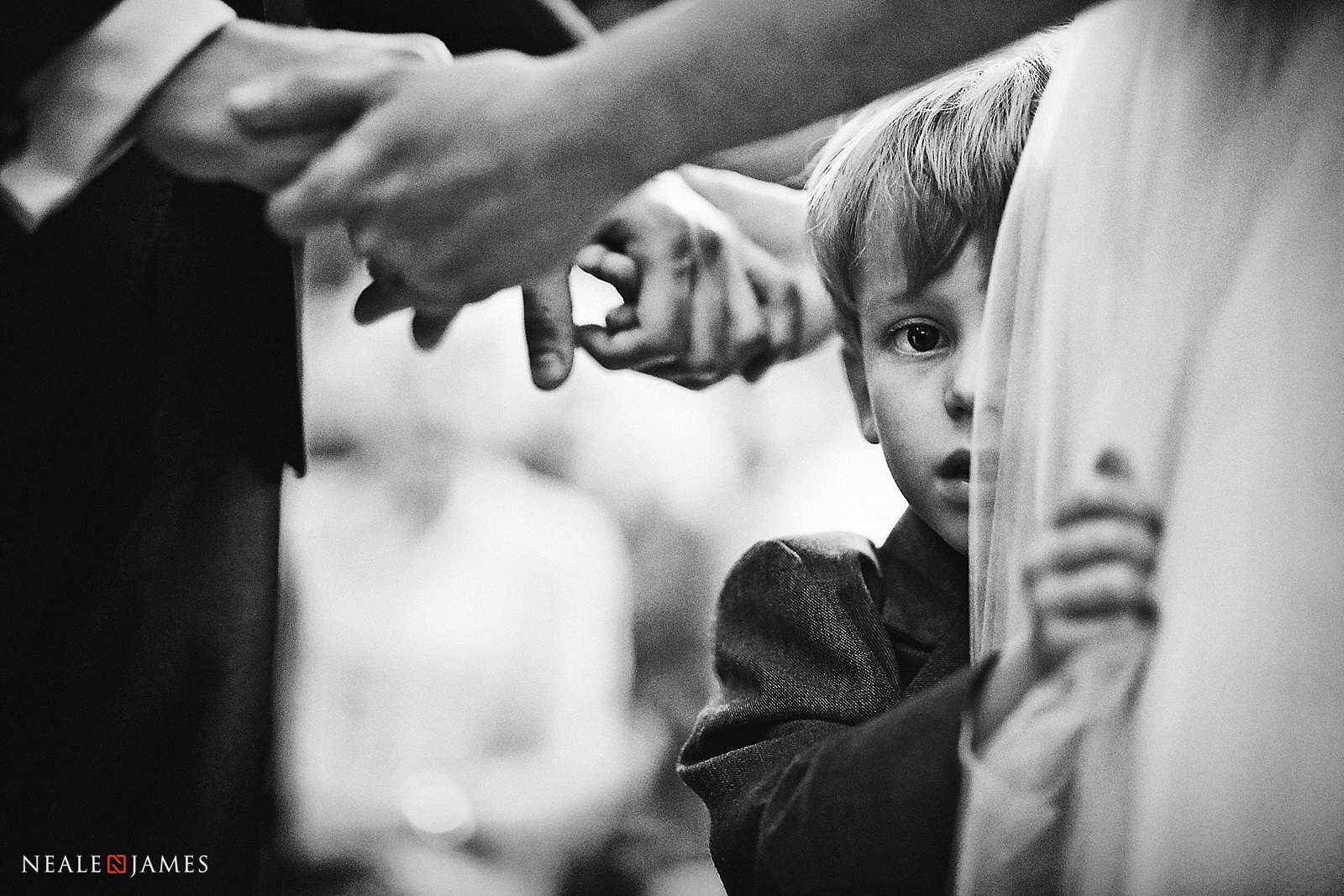 A boy peeks around his mother during this wedding in London