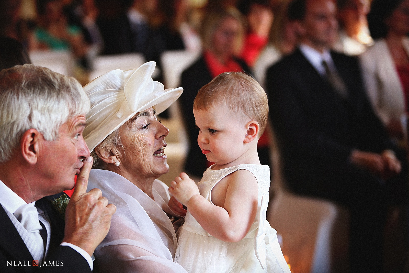 A Grandfather trying to calm a child during a wedding