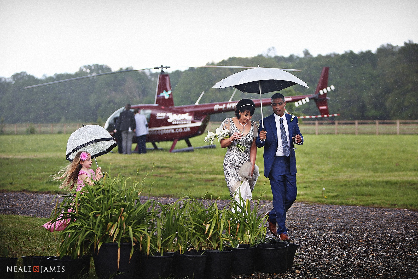 A bride and groom arrive by helicopter in the rain