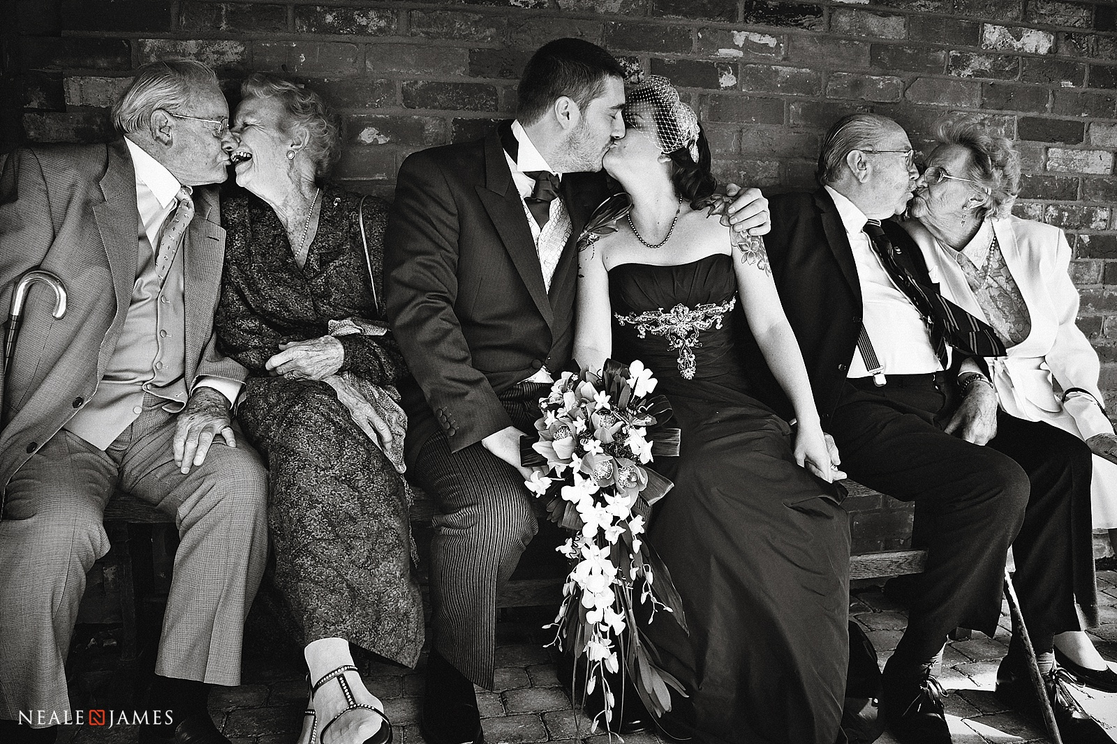 Grandparents, bride and groom kissing at this wedding in a black and white picture