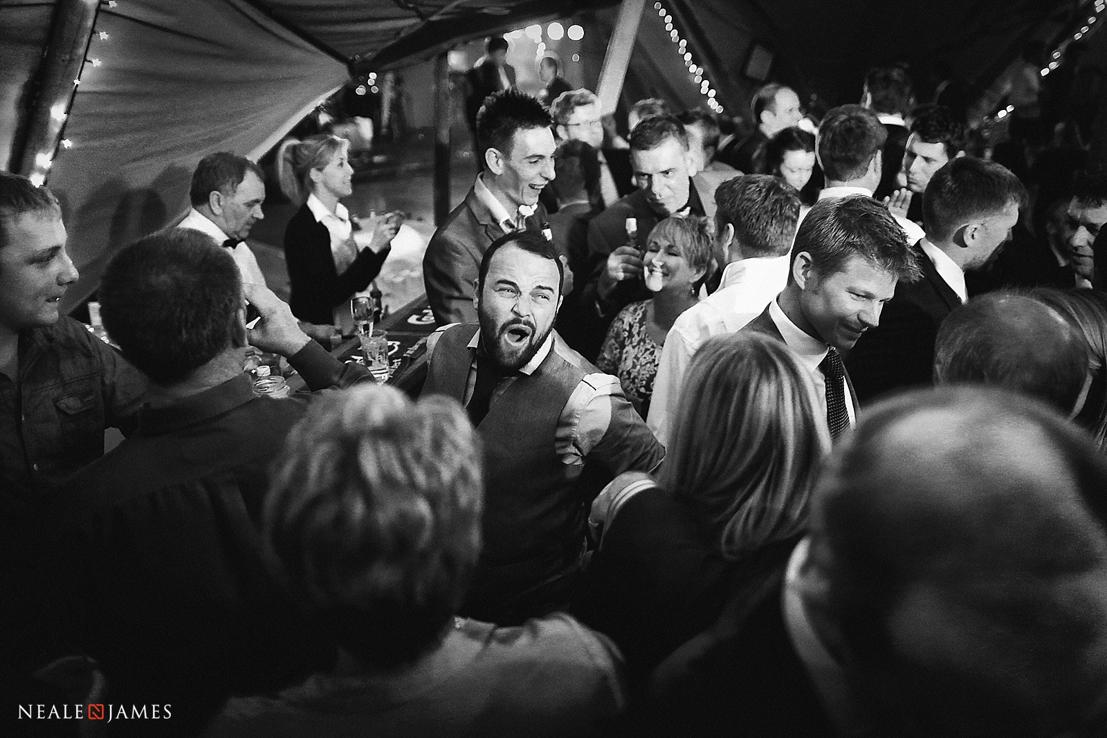 Black and white picture of a bar with guests around it at a wedding