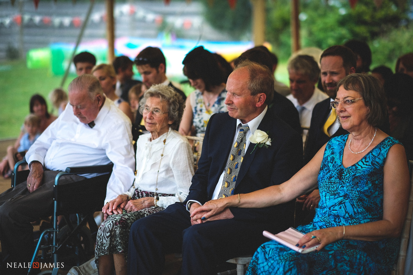 Picture of family members holding hands at a wedding