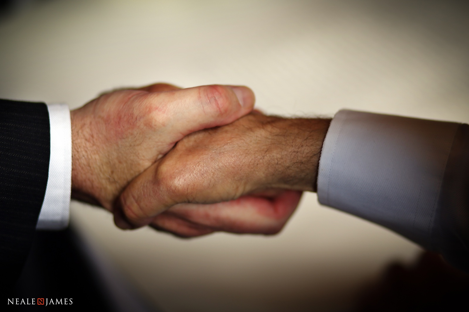 A picture of a handshake just prior to a wedding between father and groom