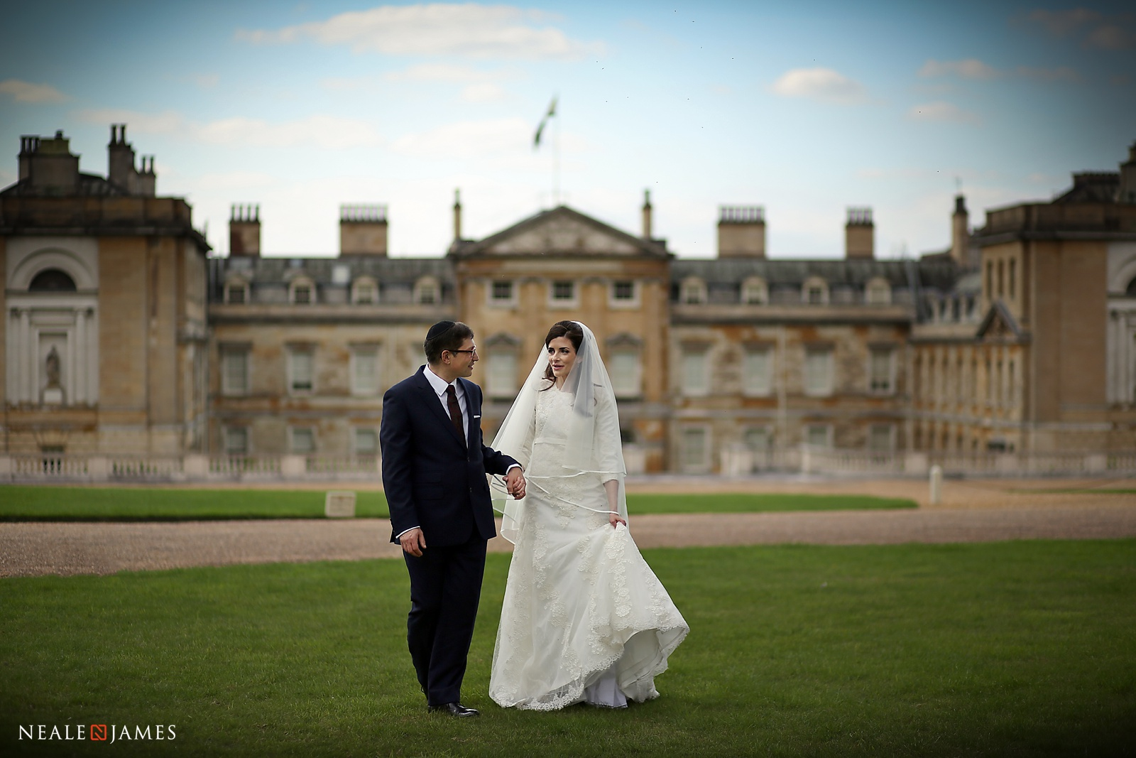 Colour photo of a bride and groom afront Woburn Abbey