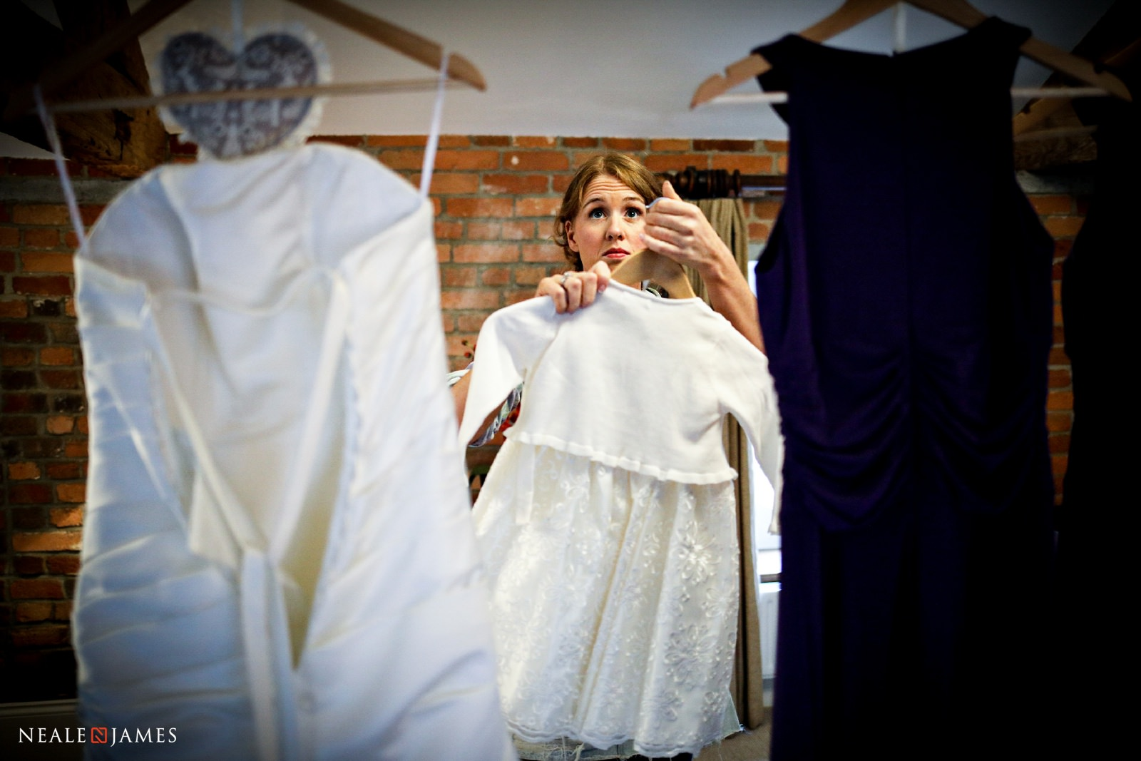 A bride hangs her dress up as she prepares for her winter wedding at Wasing Park