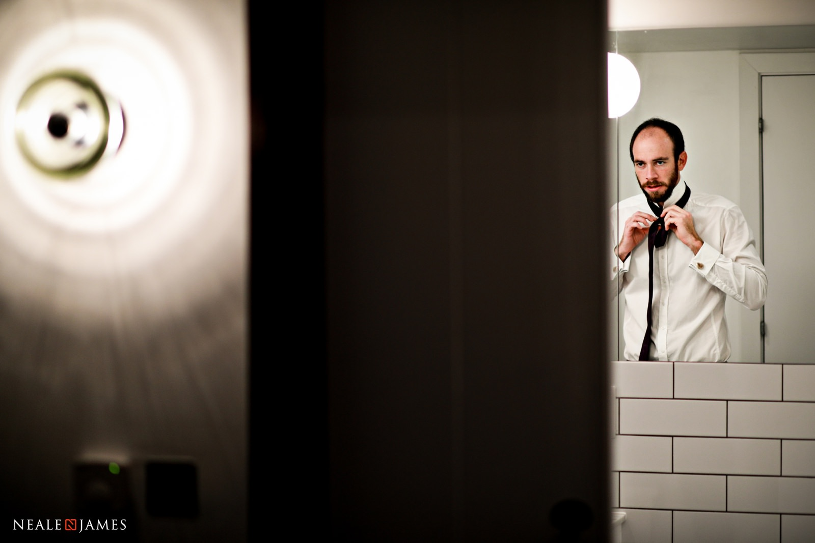 A groom looks at his reflection as he does up his tie before his wedding ceremony