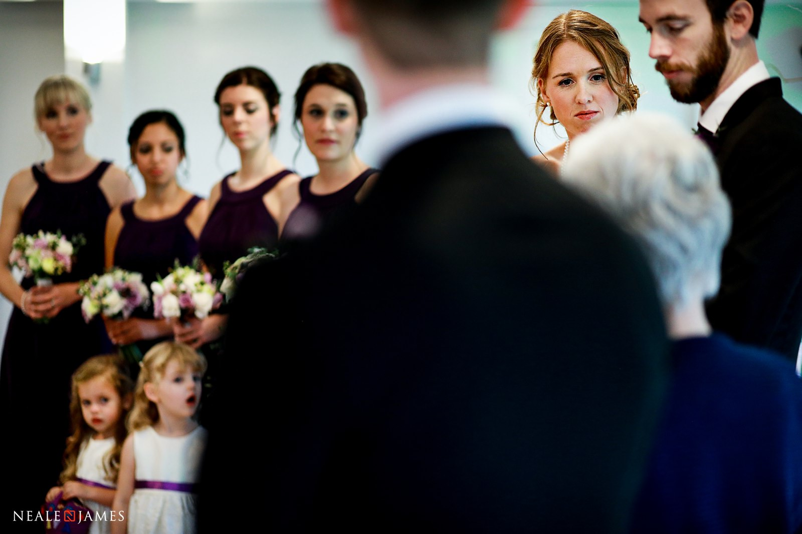 Bridesmaids look on as friends marry at Wasing Park in Berkshire